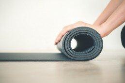 Alumno con una esterilla en una sesión de yoga para Yoga para jóvenes y adultos